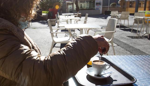 Una clienta prenent un cafè amb llet a la plaça del Poble d'Andorra la Vella.