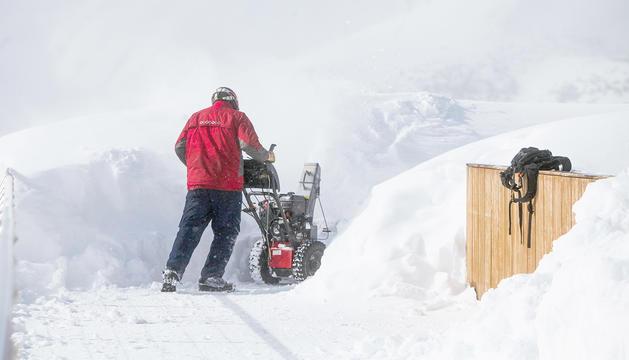 Un temporer treu neu d'una estació d'esquí.