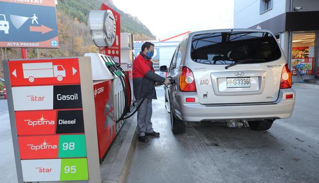 Un treballador omple el dipòsit d'un vehicle.