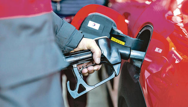 Un treballador omple el dipòsit de carburant d'un vehicle.