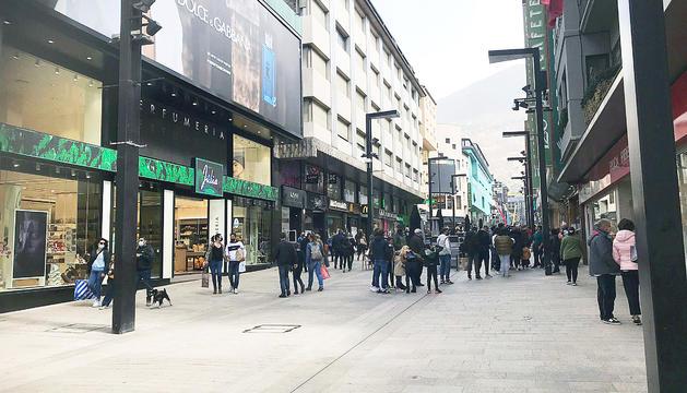 Turistes a l'avinguda Meritxell, alguns fent cua per entrar en un restaurant.