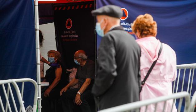 Gents vacunant-se i esperant ser vacunada