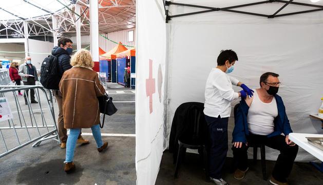 Una infermera subministrant una dosi de la vacuna a un ciutadà.