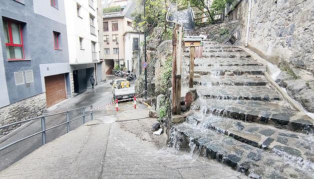 L'aigua baixant pel carrer després de caure el mur.