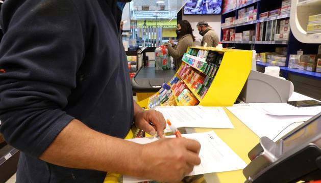 Un client signa el formulari contra la taxa en una benzinera.