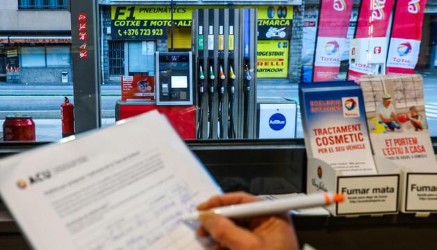 Una usuària signant un dels fulls que facilita una benzinera de la capital.