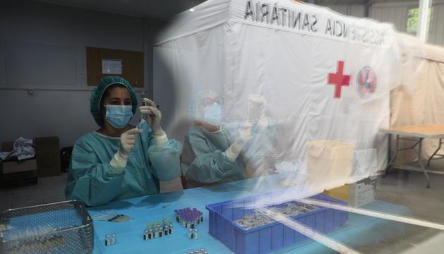 Sanitàries preparant dosis de Pfizer al centre de vacunació de la plaça de braus