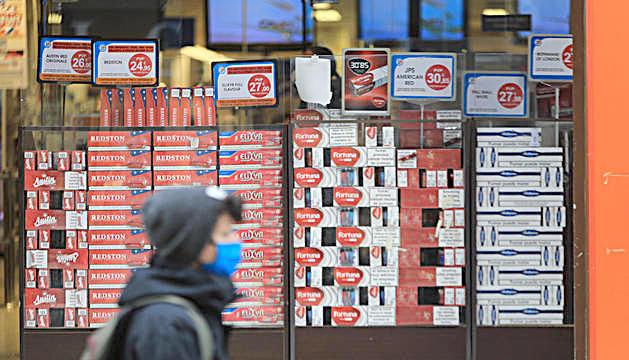 Un jove passant per davant d'un aparador amb tabac.