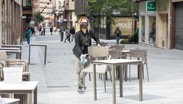 Una treballadora organitzant una terrassa del carrer Callaueta de la capital.
