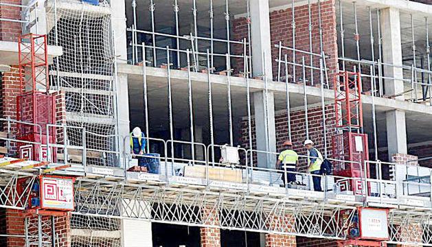 Uns obrers de la construcció treballant en un edifici.