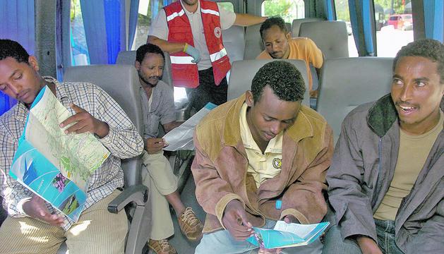 els cinc eritreus examinantf un mapa d'Andorra al microbús que els porta al país.