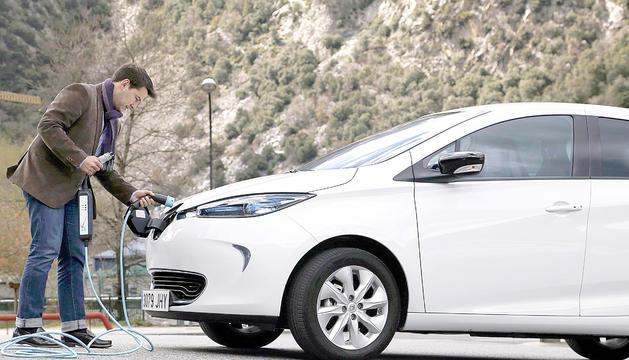 Un ciutadà posant a carregar un vehicle elèctric.