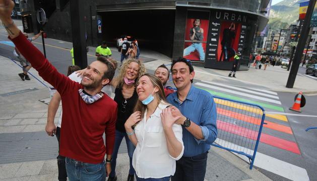 Membres de DiversAnd davant el pas pintat amb els colors LGTBI