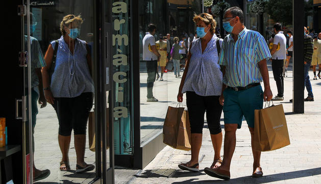 Dos turistes comprant a l'avinguda Meritxell.