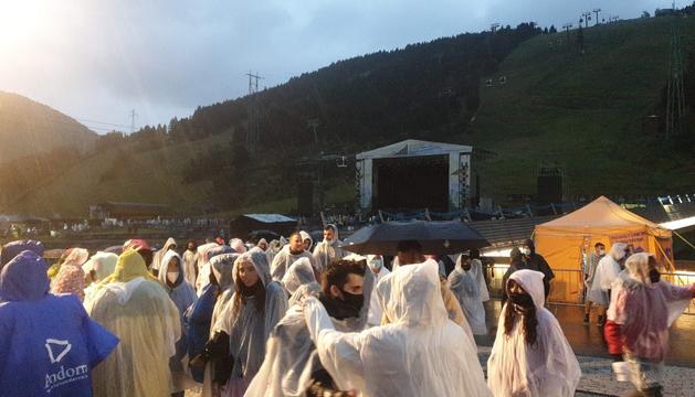 Assistents al concert protegits contra la pluja que va retardar l'actuació més d'una hora.