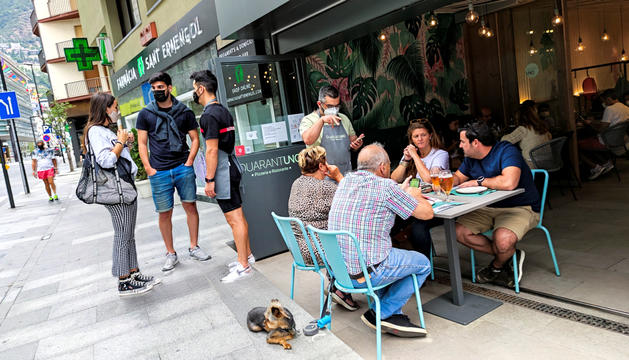 Un cambrer atenent un grup de clients en un restaurant del centre d'Andorra la Vella.