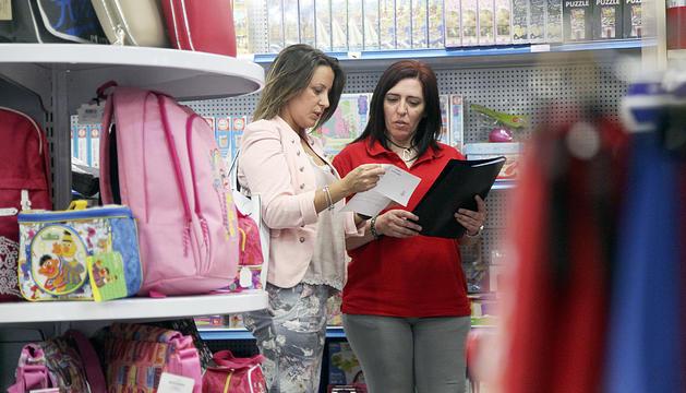 Una clienta i una dependenta repassen una llista de material escolar en una imatge d'arxiu.