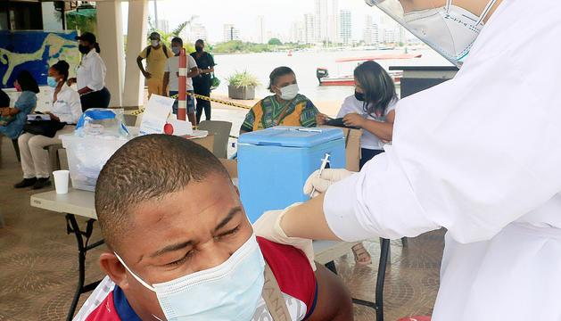 Un home rebent una dosi de la vacuna a Colòmbia.