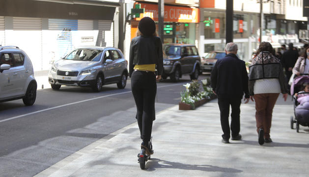 Una noia circulant amb patinet elèctric per la vorera de l'avinguda Meritxell.